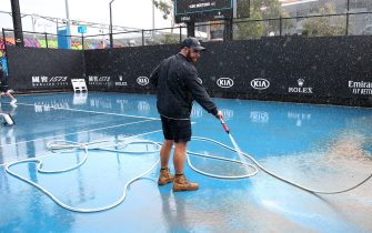 MELBOURNE, AUSTRALIA - JANUARY 23: Staff are seen attempting to clean dirt off the outside courts after being caused by rainfall on day four of the 2020 Australian Open at Melbourne Park on January 23, 2020 in Melbourne, Australia. (Photo by Mike Owen/Getty Images)