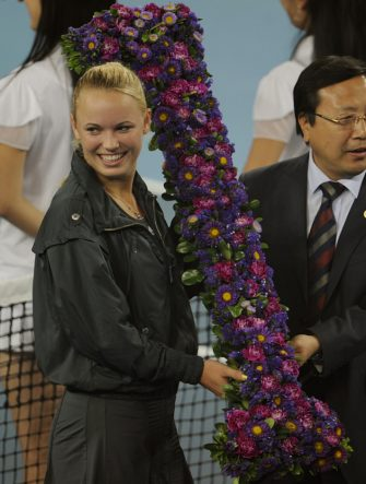 Caroline Wozniacki of Denmark (L) receives bouquet of flowers in the shape of the number one after winning her third round women's match against Petra Kvitova of Czech Republic and become the world's number one rank women's player, in the China Open tennis tournament at the National Tennis Center in Beijing on October 7, 2010. Wozniacki  beat Kvitova 6-2, 6-3.  AFP PHOTO/Peter Parks (Photo credit should read PETER PARKS/AFP via Getty Images)