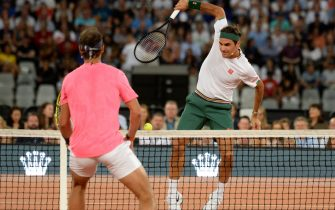 Switzerland's Roger Federer (R) plays a return to Spain's Rafael Nadal and American philanthropist Bill Gates during their double's tennis match at The Match in Africa at the Cape Town Stadium, in Cape Town on February 7, 2020. (Photo by RODGER BOSCH / AFP) (Photo by RODGER BOSCH/AFP via Getty Images)