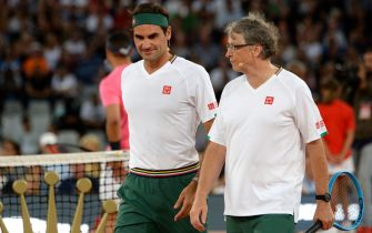 Switzerland's Roger Federer (L) and American philanthropist Bill Gates (R) walks ont the tennis court during their double's tennis match against Spain's Rafael Nadal and South African Comedian Trevor Noah at The Match in Africa at the Cape Town Stadium, in Cape Town on February 7, 2020. (Photo by RODGER BOSCH / AFP) (Photo by RODGER BOSCH/AFP via Getty Images)