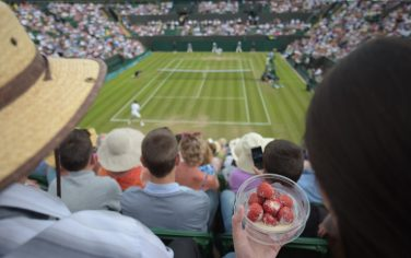 A spectator eats strawberries and cream as she watches Spain's David Ferrer play against Russia's Andrey Kuznetsov during their men's singles second round match on day three of the 2014 Wimbledon Championships at The All England Tennis Club in Wimbledon, southwest London, on June 25, 2014. AFP PHOTO / CARL COURT  - RESTRICTED TO EDITORIAL USE        (Photo credit should read CARL COURT/AFP via Getty Images)