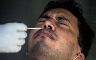 A health official collects a swab sample from a man to test for the COVID-19 coronavirus at a temporary testing center at a hotel after authorities eased restrictions imposed as a preventive measure against the spread of the COVID-19 coronavirus, in New Delhi on June 17, 2020. - India's official coronavirus death toll leapt by more than 2,000 on June 17 as the hard-hit country struggles to contain a ballooning health crisis that has overwhelmed hospitals. The news came as Germany urged its nationals in India to consider leaving for their own safety, while France warned its citizens in New Delhi to stay home unless going to an airport to return to Europe. (Photo by XAVIER GALIANA / AFP) (Photo by XAVIER GALIANA/AFP via Getty Images)