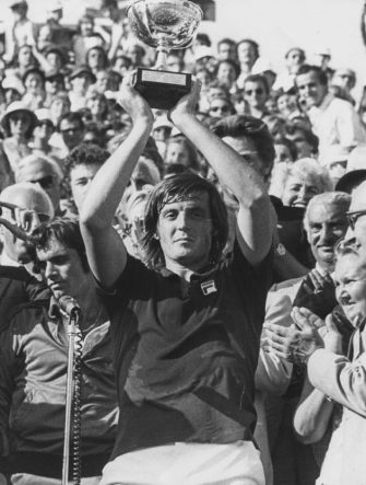 Italian tennis player Adriano Panatta holding his trophy in the air after winning the French Open Tennis Championships at Roland Garros, Paris, 1976. (Photo by Keystone/Hulton Archive/Getty Images)