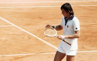 Italian tennis player Adriano Panatta looks at his broken racquet in his match against Mexican Raul Ramirez in june 1977 during the French Open at Roland Garros stadium. (Photo by - / AFP) (Photo by -/AFP via Getty Images)
