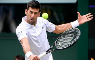 epa09328818 Novak Djokovic of Serbia hits a backhand during the men's quarter final match against Marton Fucsovics of Hungary at the Wimbledon Championships, in Wimbledon, Britain, 07 July 2021.  EPA/NEIL HALL   EDITORIAL USE ONLY