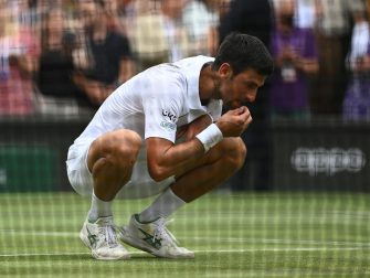 epa09337825 Novak Djokovic of Serbia tastes the grass on the court after winning the men's final against Matteo Berrettini of Italy at the Wimbledon Championships, Wimbledon, Britain 11 July 2021.  EPA/NEIL HALL   EDITORIAL USE ONLY
