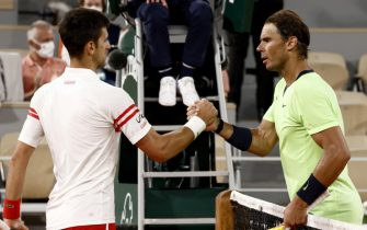 epa09263602 Novak Djokovic (L) of Serbia celebrates winning against Rafael Nadal (R) of Spain during their semi final match at the French Open tennis tournament at Roland Garros in Paris, France, 11 June 2021.  EPA/YOAN VALAT