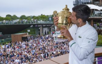 epa09338205 Spectators watching on as Novak Djokovic of Serbia poses with the Gentlemen's Singles Trophy on the balcony of the Clubhouse after winning the Gentlemen's Singles at The Wimbledon Championships tennis tournament in Wimbledon, Britain, 11 July 2021.  EPA/AELTC / Bob Martin / POOL   EDITORIAL USE ONLY