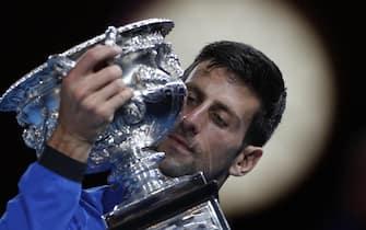 epa07325278 Novak Djokovic of Serbia holds his winners trophy after defeating Rafael Nadal of Spain in their men's singles final match at the Australian Open Grand Slam tennis tournament in Melbourne, Australia, 27 January 2019  EPA/LYNN BO BO
