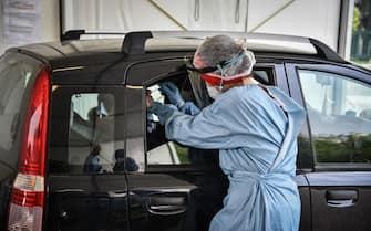 Operatrice sanitaria mentre effettua un tampone per la rilevazione del coronavirus in un drive-in