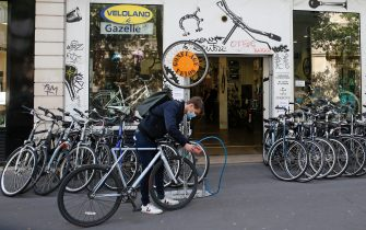 PARIS, FRANCE - MAY 13: A cyclist wearing a protective face mask inflates the tire of his bike in front of a repair cycling shop as France is slowly reopening after almost two months of strict lockdown throughout the country due to the epidemic of coronavirus (COVID 19) on May 13, 2020 in Paris, France. The French government offers a check for 50 euros for the repair of bicycles to facilitate circulation in large cities. France has begun a gradual easing of its lockdown measures and restrictions amid the coronavirus (COVID-19) outbreak. The Coronavirus (COVID-19) pandemic has spread to many countries across the world, claiming over 292,000 lives and infecting over 4.2 million people.