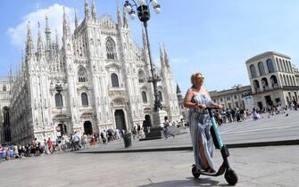 Una donna guida un monopattino in piazza Duomo a Milano, 1 agosto 2019. ANSA/DANIEL DAL ZENNARO