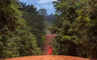 """A Waiapi man walks on the road in the Waiapi indigenous reserve in Amapa state in Brazil on October 15, 2017. Tribal chieftain Tzako Waiapi perfectly remembers the day almost half a century ago when his hunting party stumbled across a group of white adventurers in the Amazon rainforest. Within months, nearly everyone in his entire tribe had died from disease.  / AFP PHOTO / Apu Gomes / TO GO WITH AFP STORY """"When the Waipai tribe almost died out"""" by Sebastian Smith        (Photo credit should read APU GOMES/AFP via Getty Images)"""
