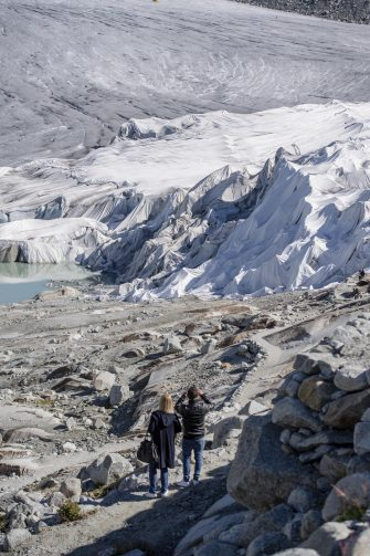 epa08553193 People visit the Rhone Glacier covered in blankets above Gletsch near the Furkapass in Switzerland, 18 July 2020. The Alps oldest glacier is protected by special white blankets to prevent it from melting.  EPA/URS FLUEELER