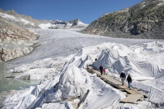 epa08553197 People visit the Rhone Glacier covered in blankets above Gletsch near the Furkapass in Switzerland, 18 July 2020. The Alps oldest glacier is protected by special white blankets to prevent it from melting.  EPA/URS FLUEELER