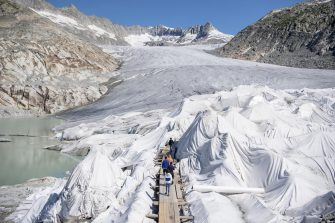 epa08553173 People visit the Rhone Glacier covered in blankets above Gletsch near the Furkapass in Switzerland, 18 July 2020. The Alps oldest glacier is protected by special white blankets to prevent it from melting.  EPA/URS FLUEELER