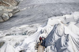 epa08553172 People visit the Rhone Glacier covered in blankets above Gletsch near the Furkapass in Switzerland, 18 July 2020. The Alps oldest glacier is protected by special white blankets to prevent it from melting.  EPA/URS FLUEELER