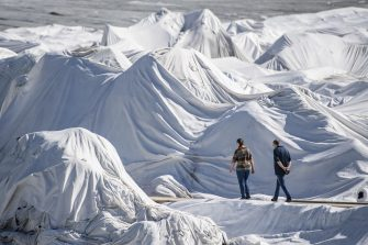 epa08553175 People visit the Rhone Glacier covered in blankets above Gletsch near the Furkapass in Switzerland, 18 July 2020. The Alps oldest glacier is protected by special white blankets to prevent it from melting.  EPA/URS FLUEELER