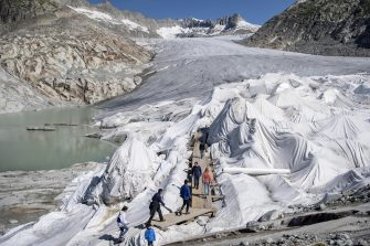 epa08553176 People visit the Rhone Glacier covered in blankets above Gletsch near the Furkapass in Switzerland, 18 July 2020. The Alps oldest glacier is protected by special white blankets to prevent it from melting.  EPA/URS FLUEELER