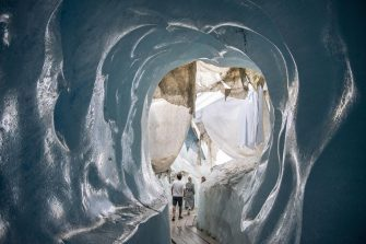 epa08553192 People visit the Ice cave in the Rhone Glacier covered in blankets above Gletsch near the Furkapass in Switzerland, 18 July 2020. The Alps oldest glacier is protected by special white blankets to prevent it from melting.  EPA/URS FLUEELER