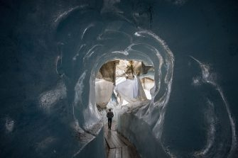 epa08553194 People visit the Ice cave in the Rhone Glacier covered in blankets above Gletsch near the Furkapass in Switzerland, 18 July 2020. The Alps oldest glacier is protected by special white blankets to prevent it from melting.  EPA/URS FLUEELER