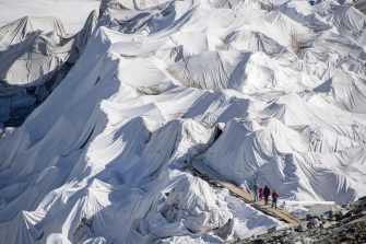 epa08553134 People visit the Rhone Glacier covered in blankets above Gletsch near the Furkapass in Switzerland, 18 July 2020. The Alps oldest glacier is protected by special white blankets to prevent it from melting.  EPA/URS FLUEELER