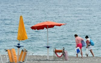 A ship of the Italian Coast Guards patrol as tourists walk along the beach near the Media Center of the G7 in the coastal town of Giardini Naxos, south of Taormina, on May 25, 2017. The small Sicilian city of Taormina hosts the summit of the leaders of the Group of Seven (G7) industrialised countries on May 26 and 27, 2017.  / AFP PHOTO / GIOVANNI ISOLINO        (Photo credit should read GIOVANNI ISOLINO/AFP via Getty Images)