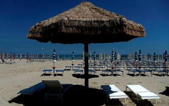 Deckchairs and a sunshade made of dried straw are pictured on the Adriatic beach of San Benedetto del Tronto on May 23, 2019. (Photo by Filippo MONTEFORTE / AFP)        (Photo credit should read FILIPPO MONTEFORTE/AFP via Getty Images)