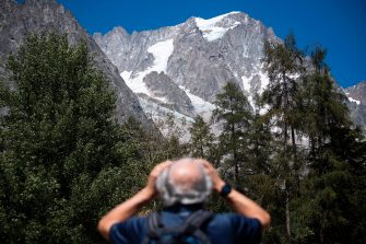 A man looks up to the Planpincieux glacier from the village of La Palud, in Courmayeur, Val Ferret, northwestern Italy, on August 6, 2020. - Several dozen people have been evacuated in northwestern Italy as a huge chunk of a glacier in the Mont Blanc massif threatens to break off due to high temperatures. (Photo by MARCO BERTORELLO / AFP) (Photo by MARCO BERTORELLO/AFP via Getty Images)
