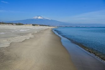 CATANIA, ITALY - APRIL 13: Playa beach empty on Easter Monday n April 13, 2020 in Catania, Italy. The beach is usually very popular with the people of Catania on sunny days. In the background the volcano Etna still with snow. Easter celebrations go on throughout Italy which remains still in lockdown due to the Coronavirus Covid-19 epidemic.  (Photo by Fabrizio Villa/Getty Images)