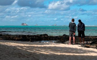Two men, near Blue Bay Marine Park, look at the vessel MV Wakashio, belonging to a Japanese company but Panamanian-flagged, on August 15, 2020 that ran aground near Blue Bay Marine Park off the coast of south-east Mauritius. - A fresh streak of oil spilled on August 14, 2020, from a ship stranded on a reef in pristine waters off Mauritius, threatening further ecological devastation as demands mount for answers as to why the vessel had come so close to shore. (Photo by Fabien Dubessay / AFP) (Photo by FABIEN DUBESSAY/AFP via Getty Images)