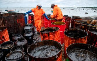 Workers collect leaked oil at the beach in Riviere des Creoles on August 15, 2020, due to the oil leaked from vessel MV Wakashio, belonging to a Japanese company but Panamanian-flagged, that ran aground near Blue Bay Marine Park off the coast of south-east Mauritius. - A fresh streak of oil spilled on August 14, 2020, from a ship stranded on a reef in pristine waters off Mauritius, threatening further ecological devastation as demands mount for answers as to why the vessel had come so close to shore. (Photo by Fabien Dubessay / AFP) (Photo by FABIEN DUBESSAY/AFP via Getty Images)