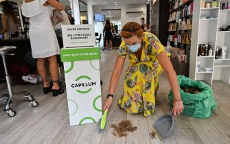 A hairdresser picks up hairs to give them to the hairdresser network of Capillum on August 14, 2020, in a hair salon in Clermont-Ferrand, central France. - Capillum is a Clermont-Ferrand based start-up specialised in hair recycling. They relayed on August 12, 2020, to its partners a call for hair donations, which can absorb hydrocarbons, to fight against the black tide in Mauritius. (Photo by PHILIPPE DESMAZES / AFP) (Photo by PHILIPPE DESMAZES/AFP via Getty Images)