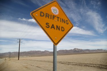 AMBOY, CALIFORNIA - SEPTEMBER 22:  A 'Drifting Sand' sign is posted in the Mojave desert on September 22, 2019 in Amboy, California. California's Fourth Climate Change Assessment found that temperatures of the inland deserts of Southern California, including the Mojave desert, are expected to continue climbing. According to the report, average daily highs could increase as much as 14 degrees this century if greenhouse gas emissions keep rising.  (Photo by Mario Tama/Getty Images)