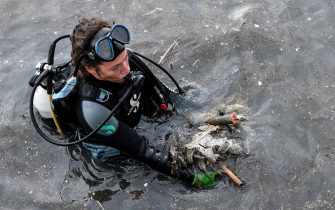 TOPSHOT - A volunteer from the Aegean Rebreath Greek organisation holds waste found in the sea at the port of the Ionian island of Zakynthos on November 23, 2019. - Within three hours a team of a dozen volunteers from Aegean Rebreath, a Greek organisation formed in 2017 to protect Aegean biodiversity from waste, collects four tyres, two shopping carts, a street lamp, metal boxes, plastic bags, dozens of plastic bottles and several kilometres of fishing line. In its two years of operation, Aegean Rebreath has amassed 9,000 plastic water bottles, 3,6 tons of fishing net and 289 tyres. The Mediterranean, a partly closed sea, accumulates 570,000 tons of plastic annually from surrounding countries, according to the World Wildlife Fund. (Photo by LOUISA GOULIAMAKI / AFP) (Photo by LOUISA GOULIAMAKI/AFP via Getty Images)
