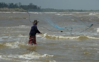 A fishermen casts a net by the sea along shore of Thailand's southern province of Narathiwat on Decmeber 5, 2019. (Photo by Madaree TOHLALA / AFP) (Photo by MADAREE TOHLALA/AFP via Getty Images)