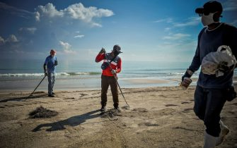 Workers wearing face masks clean the beach east of Havana on June 15, 2020 as Cuba prepares for a gradual reopening of the country amid the COVID-19 coronavirus pandemic. - Cuba is planning to welcome tourists with COVID-19 tests and limit their contact with locals as part of a raft of measures designed to get its vital tourism industry back up and running. The government of President Miguel Diaz-Canel said it would gradually open up the economy in the next weeks, with a particular focus on recovering tourism dollars lost to the lockdown. (Photo by Yamil LAGE / AFP) (Photo by YAMIL LAGE/AFP via Getty Images)