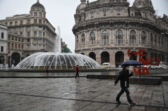 People wearing a protection mask walk across Piazza Raffaele de Ferrari in Genoa, Liguria, on March 13, 2020 as Italy shut all stores except for pharmacies and food shops in a desperate bid to halt the spread of a coronavirus. (Photo by Marco BERTORELLO / AFP) (Photo by MARCO BERTORELLO/AFP via Getty Images)