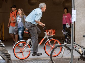 """A man rides a Mobike throught the streets of Washington, DC, on September 20, 2017, after about 200 of the bicycles that are rented via an app that finds the closest bicycle via GPS became available for public use. Chinese bike-sharing giant Mobike on Wednesday launched in the US capital, bringing its """"dockless"""" system which has swept China and is used in some 180 cities worldwide. / AFP PHOTO / PAUL J. RICHARDS        (Photo credit should read PAUL J. RICHARDS/AFP via Getty Images)"""