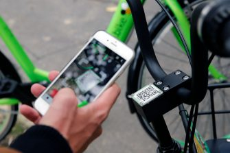 """PARIS, FRANCE - OCTOBER 10:  a man scans the QR code on a bike from the sharing service company """"Gobee.bike"""".  The Hong Kong start-up """"Gobee.bike"""" launches a city bike-sharing service in Paris. Its green bicycles are available self-service and can be borrowed and parked in any bicycle parking. The bikes are geolocated on the Gobee.bike application, allowing to see those available in the surrounding area. A unique """"QR code"""" allows to unlock the bike at the time of the instant reservation.  (Photo by Chesnot/Getty Images)"""