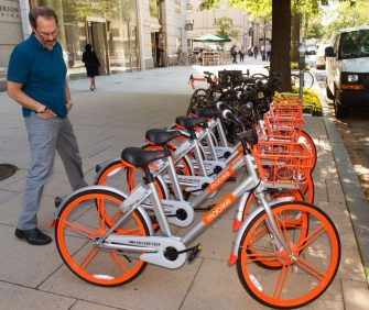 """A man looks over  Mobikes on the streets of Washington, DC, on September 20, 2017, after about 200 of the bicycles that are rented via an app that finds the closest bicycle via GPS became available for public use. - Chinese bike-sharing giant Mobike on Wednesday launched in the US capital, bringing its """"dockless"""" system which has swept China and is used in some 180 cities worldwide. (Photo by Paul J. RICHARDS / AFP)        (Photo credit should read PAUL J. RICHARDS/AFP via Getty Images)"""
