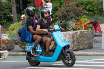NEW YORK, NEW YORK - SEPTEMBER 09: People with and without masks ride on a Revel electric scooter as the city continues Phase 4 of re-opening following restrictions imposed to slow the spread of coronavirus on September 09, 2020 in New York City. The fourth phase allows outdoor arts and entertainment, sporting events without fans and media production. (Photo by Alexi Rosenfeld/Getty Images)