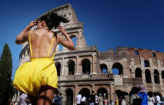 A tourist walks under the sun in front of the Colosseum in Rome on June 25, 2019 during a heatwave. - Meteorologists blamed a blast of torrid air from the Sahara for the unusually early summer heatwave, which could send thermometers up to 40 degrees Celsius (104 Fahrenheit) across large swathes of the continent. (Photo by Alberto PIZZOLI / AFP)        (Photo credit should read ALBERTO PIZZOLI/AFP via Getty Images)