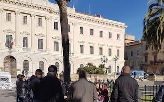 Un piccolo gruppo di allevatori attende la fine del vertice all'esterno della prefettura di Sassari, 26 febbraio 2019. ANSA/GIAN MARIO SIAS