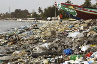 """A picture taken on June 2, 2018, shows people walking on a beach covered with trash, including many plastic items, in the Hann Bay in Dakar. - World Environment  Day is marked annually on June 5, and aims at promoting awareness and action to protect the environment. Each World Environment Day is focused on a theme that spotlights a pressing environmental concern, with the theme for 2018 being Beat Plastic Pollution"""". (Photo by SEYLLOU / AFP)        (Photo credit should read SEYLLOU/AFP via Getty Images)"""