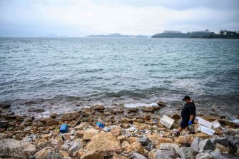 In this photo taken on May 13, 2020, Gary Stokes, founder of the environmental group Oceans Asia, uses surgical gloves to pick up discarded face masks on a polluted area of a beach in the residential area of Discovery Bay on the outlying Lantau island in Hong Kong. - Surgical masks are washing up in growing quantities on the shores of Hong Kong, a city that has overwhelmingly embraced face coverings to fight the coronavirus. Conservationists say the masks are adding to already alarmingly high levels of plastic waste in the waters around the finance hub. (Photo by Anthony WALLACE / AFP) (Photo by ANTHONY WALLACE/AFP via Getty Images)