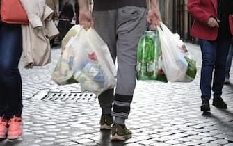 Un uomo con le buste della spesa e una confezione di acqua in bottiglie di plastica dopo l'acquisto in un supermercato di Roma, 1 novembre 2019. ANSA/LUCIANO DEL CASTILLO