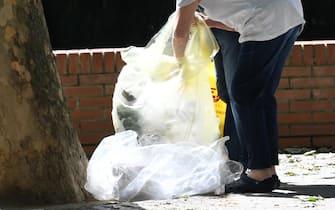 Due anziani cercano oggetti in sacchetti diplasticaabbandonati di un mercato rionale a Milano, 19 maggio 2021