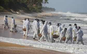 epa09244355 Sri Lanka Navy personnel, wearing protective gear, clear the beach from debris and other materials that washed ashore from the crippled container cargo vessel  MV X-Press Pearl, on the beach of Negombo, north-west of Colombo, Sri Lanka, 02 June 2021 (issued 03 June 2021). The fire on the Singaporean flagged container cargo vessel MV X-Press Pearl was doused and the salvage company began towing it towards deeper seas off the coast of Colombo on 02 June. However, the Sri Lanka Navy stated that the towing operation was halted as the stern of the ship was striking the seabed. Sri Lankan marine and coastal protection authorities warned about an environmental crisis as tonnes of plastic waste and pellets from the ship keep washing ashore. The island s Fisheries Ministry urged fishermen not to venture out to seas in the 80 km stretch along the western coast. Authorities such as the Marine Environmental Protection Authority (MEPA) are concerned over possible threats to the fish-breeding shallow waters of lagoons dotting the area, which is well known for its crabs and jumbo prawns as well as for its tourist beaches. MEPA is assessing the possible impacts on the mangroves, lagoons and marine wildlife in the region, while a possible oil leak would add to the devastation.  EPA/CHAMILA KARUNARATHNE