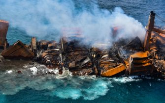 epa09243156 A handout photo made available by the Sri Lankan Air force Mediashows thefire gutted and crippled Singapore-registered container cargo vessel, MV X-Press Pearl, on the9 nautical miles northwest of Colombo port in Colombo, Sri Lanka, 02 June 2021. The fire on the Singaporean flagged container cargo vessel MV X-Press Pearl, which had been burning for over 13 days, was doused and the salvage company began towing it towards deeper seas off the coast of Colombo on 02 June. However, latest reports by the Sri Lanka Navy stated that the towing operation had been halted as the stern of the ship was striking the seabed. They also reported that so far no oil spills have been observed. A huge amount of plastic granules and debris has already washed ashore on beaches from Colombo to Negombo and authorities now fear another wave of massive pollution should the 278 tonnes of bunker oil and 50 tonnes of gas in the Singapore-registered ship's fuel tanks leak into the Indian Ocean.  EPA/SRI LANKAN AIR FORCE MEDIA HANDOUT  HANDOUT EDITORIAL USE ONLY/NO SALES